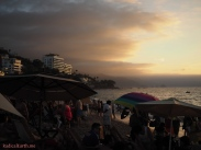 A busy Christmas week on Los Muertos beach, with misty peach clouds gathering in the foothills of the mountains to the South, in Puerto Vallarta.