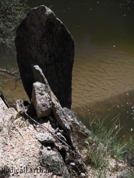 A rock is poised above a sandy spit in the Salmon River